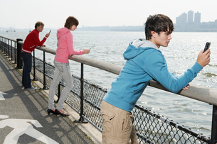 Three teenagers using mobile phoneの写真素材 [FYI02945356]