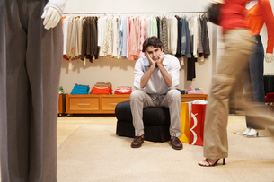 Bored man in women's clothing storeの写真素材 [FYI02945383]