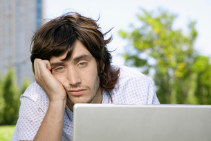 Bored young man using laptopの写真素材 [FYI02945396]