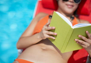 Mid-Adult Woman Reading Book by Poolの写真素材 [FYI02945434]