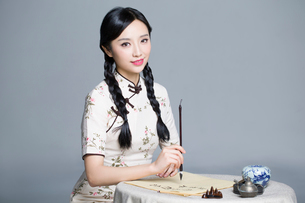 Young beautiful woman in traditional cheongsam practicing calligraphyの写真素材 [FYI02945449]