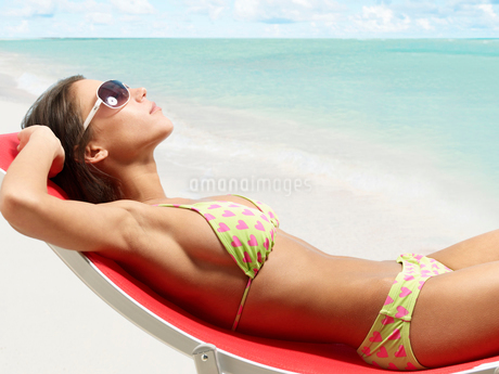 Young Woman Sunbathing on Lounge Chairの写真素材 [FYI02945461]