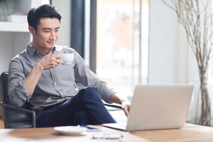 Young man drinking coffee in officeの写真素材 [FYI02945467]