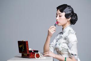 Young beautiful woman in traditional cheongsam applying lipstickの写真素材 [FYI02945468]