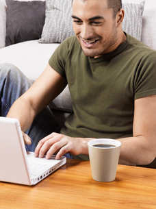 Young man using laptop on coffee tableの写真素材 [FYI02945469]