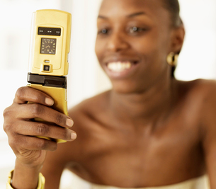 Woman Text Messaging with Golden Phoneの写真素材 [FYI02945480]