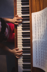 Overhead view of girl playing piano in classroomの写真素材 [FYI02945493]