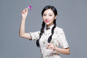 Young beautiful woman in traditional cheongsam with orchidの写真素材 [FYI02945502]