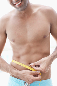 Young man measuring waist (midsection)の写真素材 [FYI02945546]