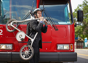 Businessman Carrying Bicycle with Bus in Backgroundの写真素材 [FYI02945602]