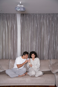 Couple eating ice cream and watching TVの写真素材 [FYI02945619]