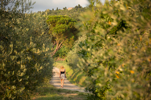 Italy, Tuscany, Dicomano, Woman walking along road in vineyardの写真素材 [FYI02945655]