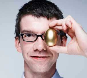 Mid-Adult Man Holding Egg to His Eyeの写真素材 [FYI02945657]