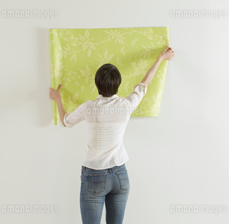 Young Woman Holding Wallpaper on Wallの写真素材 [FYI02945662]
