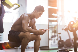 Young man using smart phone in gymの写真素材 [FYI02945708]