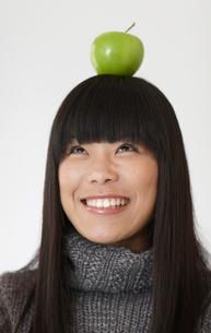 Single Apple On Top Of Woman's Headの写真素材 [FYI02945719]