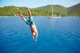 Mid adult man jumping into waterの写真素材 [FYI02945783]
