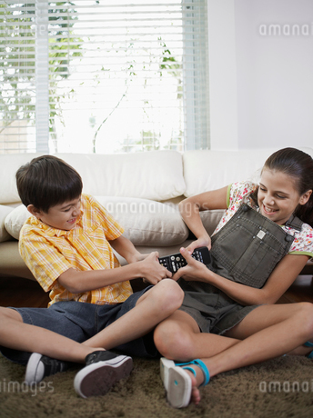 Siblings Fighting Over Remote Controlの写真素材 [FYI02945798]
