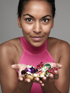 Young woman with candies in handsの写真素材 [FYI02945803]