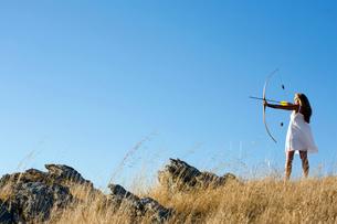 Young woman arrow shooting in fieldの写真素材 [FYI02945807]