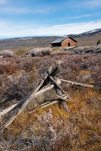 Broken fencing on grassland, and a barn in the open in the Green River lakes area.の写真素材 [FYI02945810]