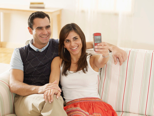 Couple Picture Messaging on Sofaの写真素材 [FYI02945817]