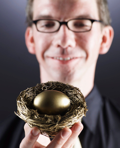 Man Holding Nest with Golden Eggの写真素材 [FYI02945823]