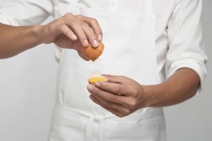 Chef cracking brown egg (mid section)の写真素材 [FYI02945830]
