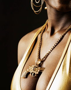 Woman Wearing Golden Gun Pendantの写真素材 [FYI02945897]
