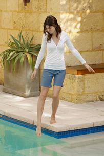 Woman testing water in swimming poolの写真素材 [FYI02945899]