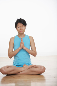 Mid Adult Woman Meditating in Lotus Positionの写真素材 [FYI02945922]