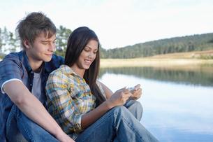 Teenage couple using mobile phoneの写真素材 [FYI02945927]