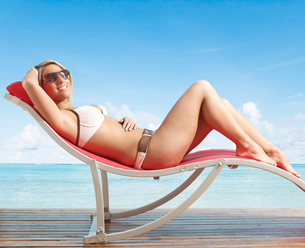 Young Woman Relaxing on Lounge Chairの写真素材 [FYI02945938]