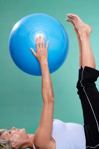 Mature woman exercising with Swiss ballの写真素材 [FYI02945980]