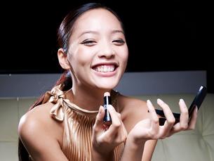 Mid-Adult Woman Applying Lipstickの写真素材 [FYI02946007]