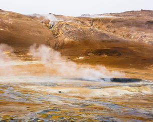 Iceland, Nordurland eystra, Hverarond, Steam over hot springs with mountain range on horizonの写真素材 [FYI02946075]