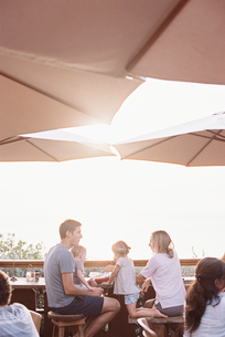 Couple sitting under a parasol in a restaurant with their son and daughter.の写真素材 [FYI02946090]