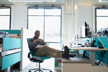 African American businessman working with feet up at office deskの写真素材 [FYI02946116]