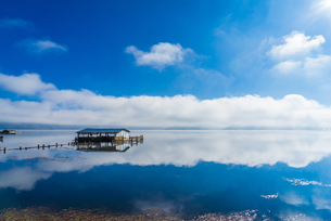Lonely cabin on the lake and reflection of sky and cloud; sunlight; Napa Hai Nature Reserve; Shangriの写真素材 [FYI02946252]
