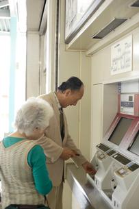 駅の券売機で切符を購入するシニア夫婦の写真素材 [FYI02946501]
