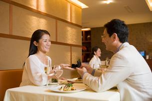 レストランで指輪の受け渡しをする夫婦の写真素材 [FYI02946651]