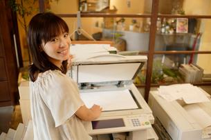 コピー機の前に立ちこちらを見る女性の写真素材 [FYI02946781]