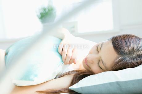 ベッドで寝ている女性の写真素材 [FYI02947058]
