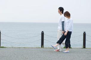 海沿いを散歩するカップルの写真素材 [FYI02947082]
