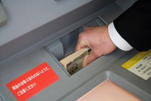 ATMにお金を入れるビジネスマンの写真素材 [FYI02947134]
