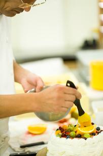 ケーキのデコレーションフルーツを仕上げるパティシエの写真素材 [FYI02947719]