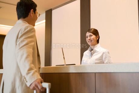 フロントに来た男性客を笑顔で迎える従業員の写真素材 [FYI02947792]