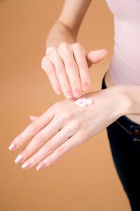化粧品を塗ろうとする女性の手の写真素材 [FYI02947906]