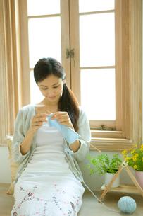 チャービルと花を置いた窓際で編み物をする女性の写真素材 [FYI02947987]