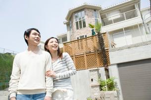 家の前で遠くを見る夫婦の写真素材 [FYI02948131]